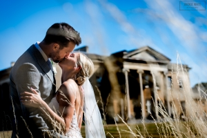 A bride and groom kiss in the sunshine outside Leigh Court, a wedding venue in Bristol