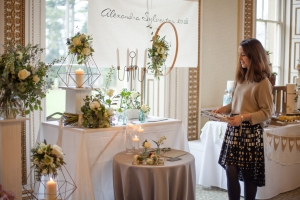 A young woman stands in front of a florist stall at the Bristol Wedding Show at Leigh Court
