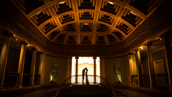 A silhouette of a bride and groom dancing on the Great Hall balcony at Leigh Court