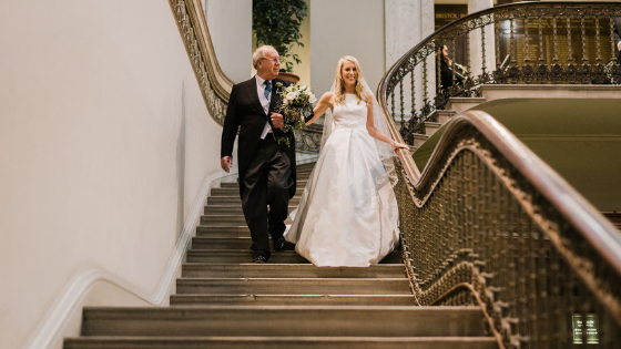 A bride is escorted down the staircase by her father at a wedding at Leigh Court