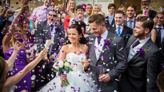 A smiling bride and groom are showered in confetti outside Leigh Court