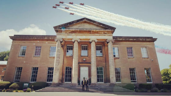 The red arrows fly over Leigh Court as a groom and groom pose in front of the mansion