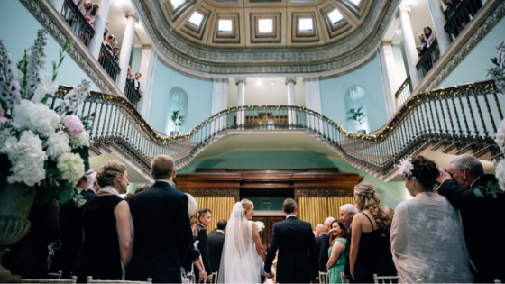 A bride and groom enter the Great Hall for their wedding ceremony at Leigh Court