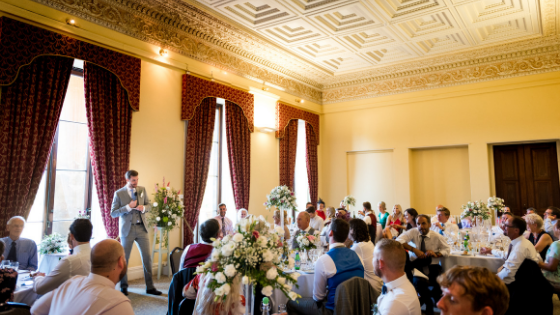 A groom is giving a speech in a large yellow room at his Leigh Court wedding