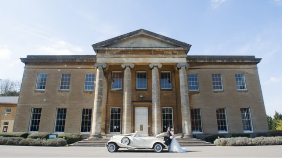 A bride and groom pose with a classic white wedding car outside Leigh Court