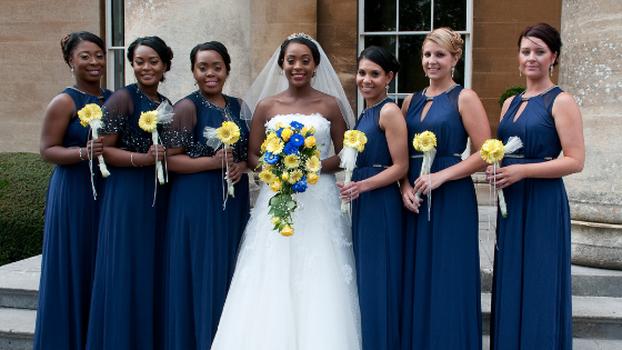 A bride and her bridesmaids on the steps of Leigh Court