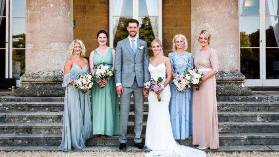A bride and groom pose with bridesmaids on the steps outside Leigh Court